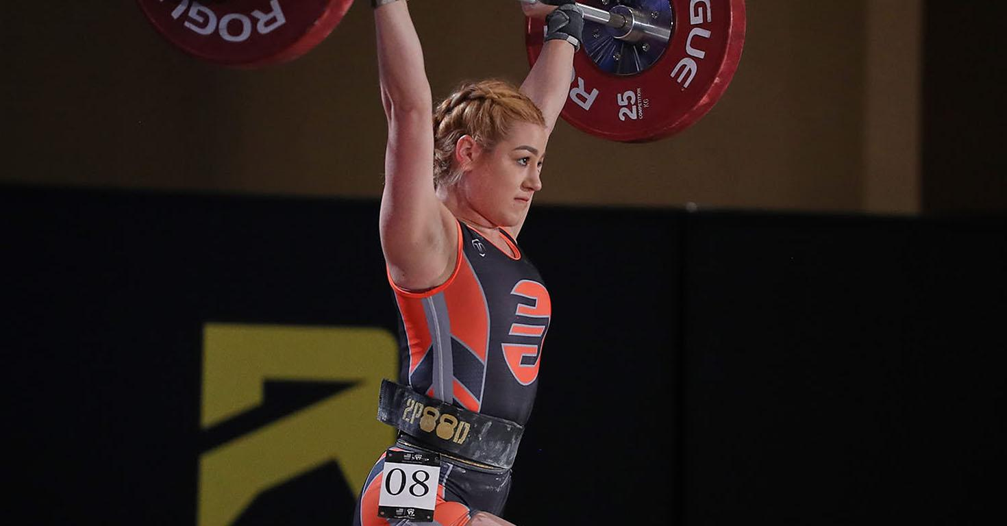 ASU student Yuliana Lopez lifts a large barbell above her head at a competition